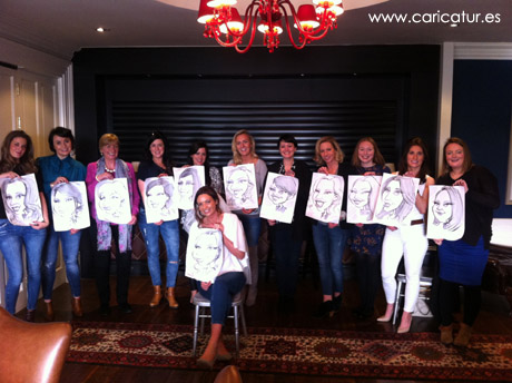 Women in hen party holding their caricatures by Allan Cavanagh