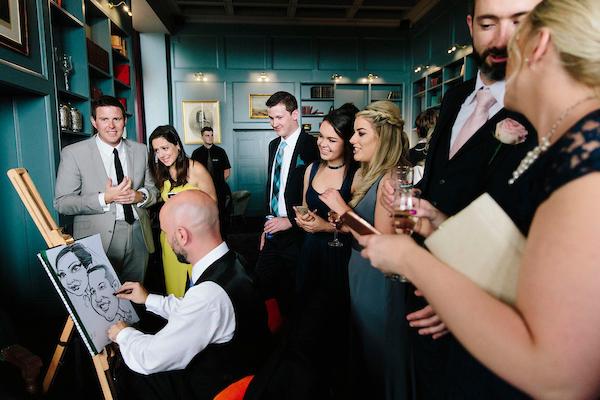 Wedding guests watching caricature artist Allan Cavanagh drawing