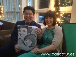 Couple holding live caricature at wedding by Allan Cavanagh