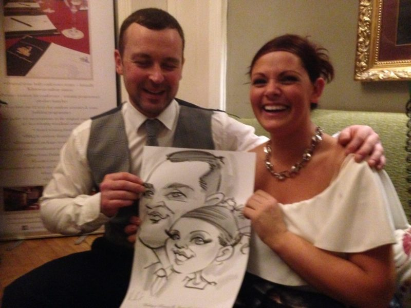 Photo of man and woman laughing with caricature by Allan Cavanagh