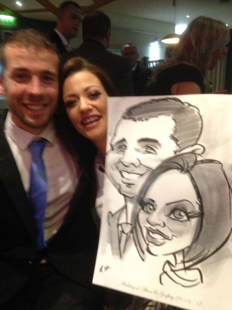 Wedding guests holding caricature by artist Allan Cavanagh