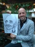 Man in grey top with live caricature by Allan Cavanagh