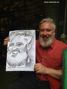 Staff parties: man with beard in red shirt holding caricature